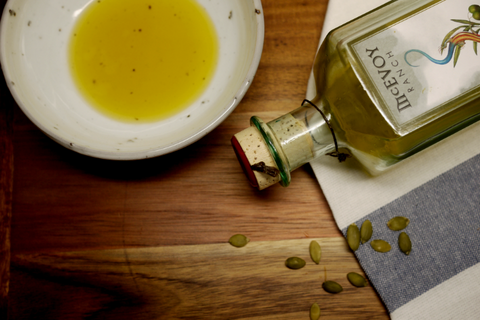 A bottle of McEvoy Extra Virgin Olive Oil with a bowl of olive oil placed on the table