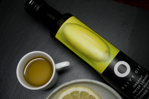A bottle of Meyer Lemon Olive Oil placed on the table along with a slice of lemon