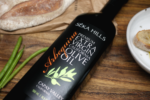 A 500ml bottle of Seka Hills Arbequina olive oil placed on the table with a slice of bread