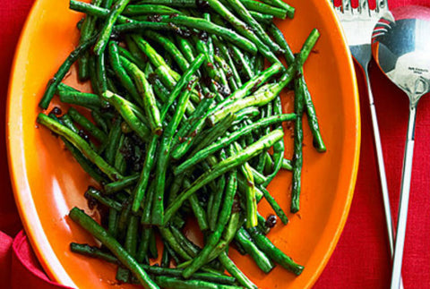 Spicy green beans cooked with chili oil sauce placed on an orange plate.