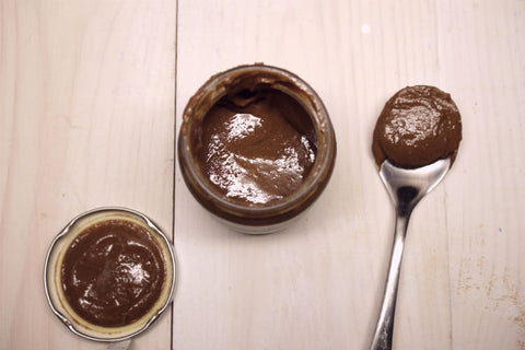 An opened jar of chocolate pumpkin seed butter placed on the table along with a table spoon.