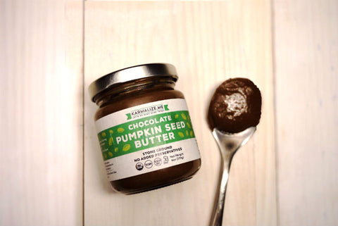 6oz jar of chocolate pumpkin seed butter placed on the table with a spoon.