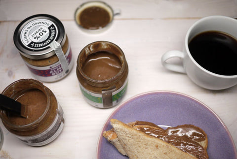 Three specialty nut butters with almond butter sandwich on the table top.