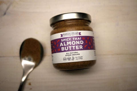 6oz jar of spicy Thai almond butter laid on the table along with a table spoon.