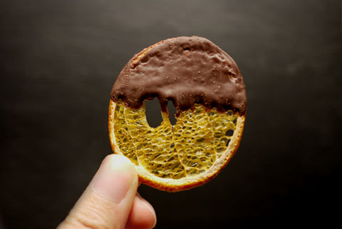 A front view of a thin dehydrated orange slice dipped with dark chocolate.