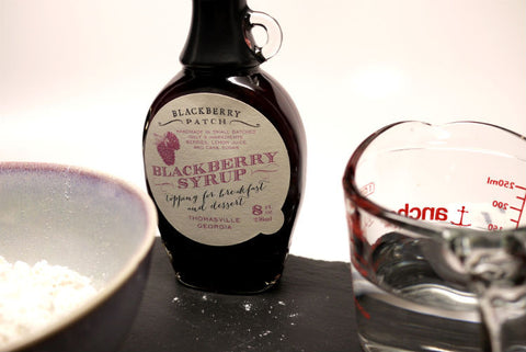 A bottle of blackberry syrup placed on the table along with a measure cup and a bowl of flour.