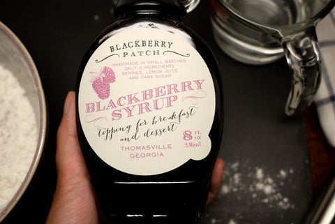 A hand is holding a 8oz bottle of blackberry syrup