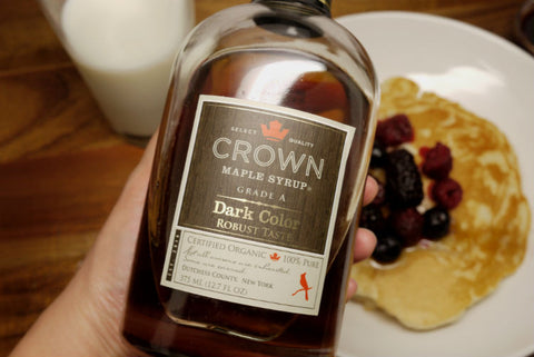 Close-up of a 350ml bottle of Crown maple syrup with a background of pancakes.
