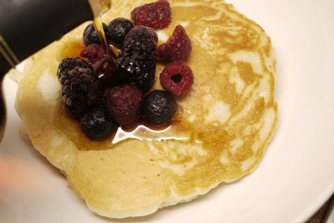 Close-up of pouring a maple syrup over pancakes and mixed berry toppings
