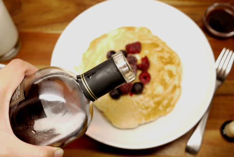 Pouring maple syrup over pancakes.