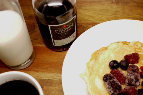 A bottle of Crown maple syrup with pancakes with berries topping and a glass of milk.