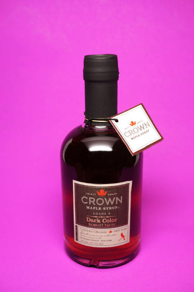 A 375ml bottle of Crown Maple Syrup in front of pink background