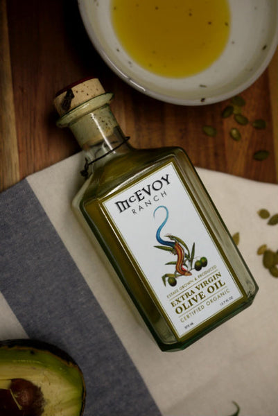 A green bottle of McEvoy Ranch Olive Oil placed on the table cloth