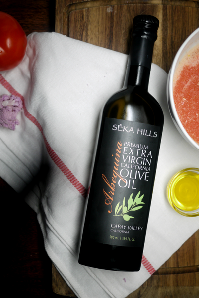 A 500ml bottle of Seka Hills Extra Virgin Olive Oil placed on the white dinner napkin