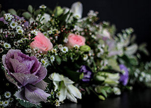 Mystic Spray features kale, cabbages, roses, lilies, lisianthus and daisies.