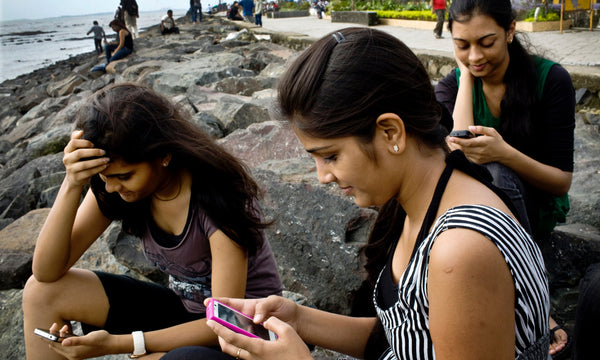Indian girls playing on social media on their phones