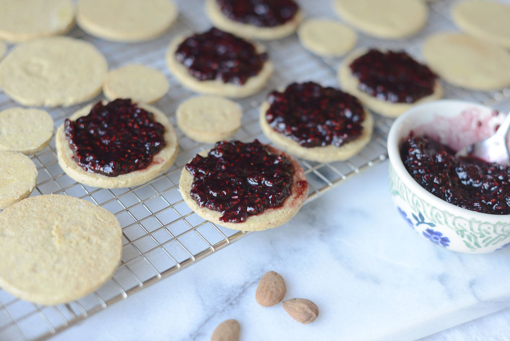 Vegan Linzer Christmas cookies adding raspberry filling