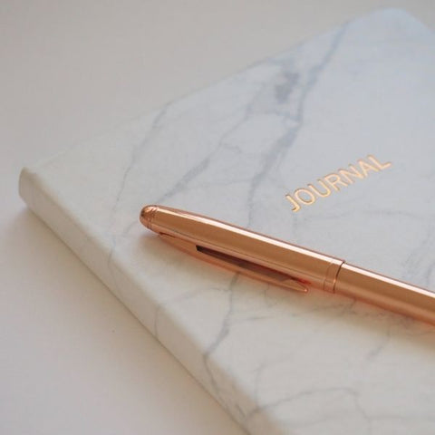 A marble journal resting on a work desk with a gold pen