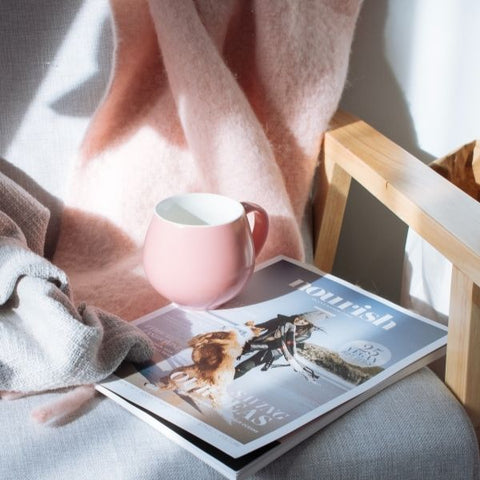 A pink coffee mug resting on a magazine on rocking chair