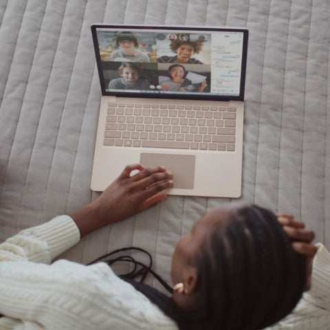 A young women lying on her bed on chatting to her family on a video call