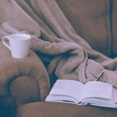 A notebook and a cup of tea resting on a sofa with a cosy blanket