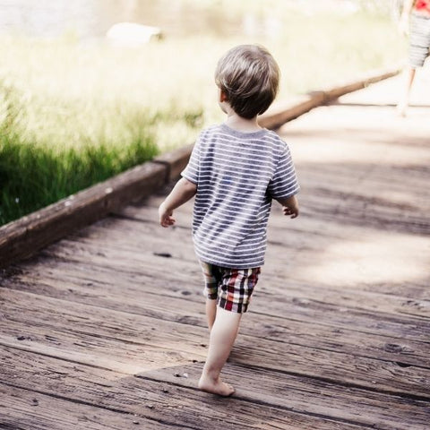 A child walking across a wooden bridge by a lake