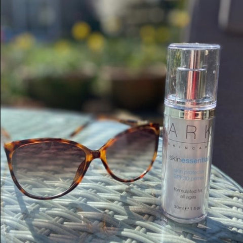 ARK Skincare's SPF 30 Primer with sunglasses outside in the sunshine
