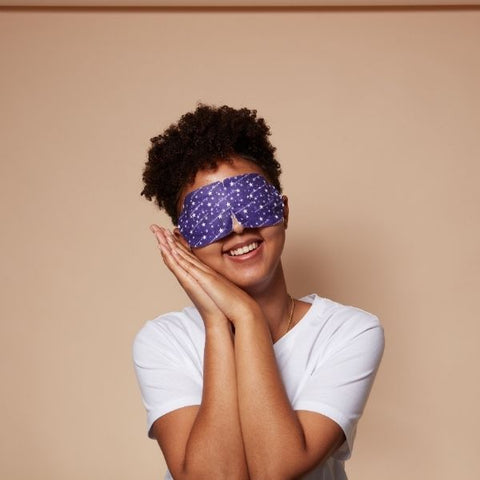 A woman posing as if she is a sleep wearing a spacemask (self heating eye mask) over her eyes
