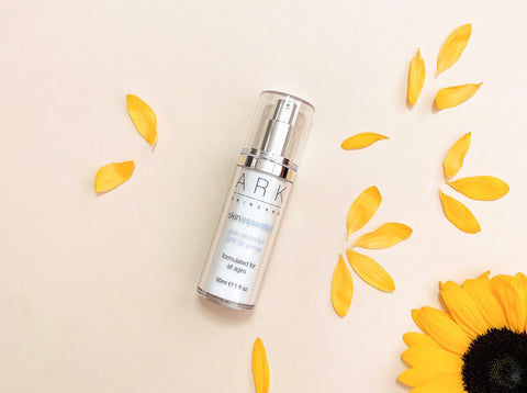 Product Image of ARK Skincare's SPF 30 Primer on a cream background next to a sunflower and vibrant yellow petals.