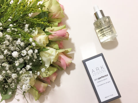 Flatlay of ARK Skincare's Radiance Serum and carton laid beside some flowers