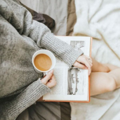 Image: Girl resting her reading book and cup of tea on her lap.