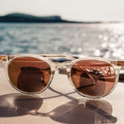 Image showing rose-gold sunglasses resting on a sun bed with the ocean in the background