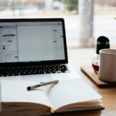 Image: laptop, diary and a coffee mug on a work desk