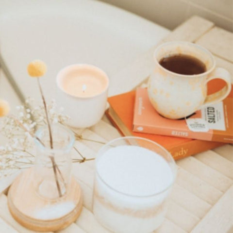 Image: A white bathtub with a bath tray/table with a cup of tea, candle and flowers.