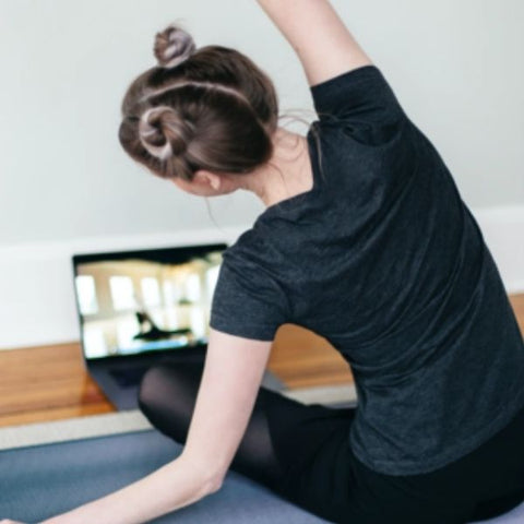 Image: Woman practicing stretches in front of her laptop, watching a live workout