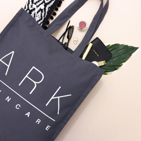 Image: ARK Skincare's Reusable cotton grey tote bag with a scarf, makeup and purse inside (lifestyle image)
