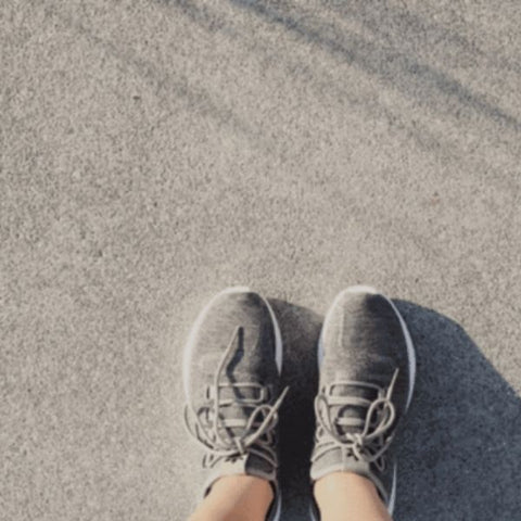 Image: A persons feet in grey running shoes