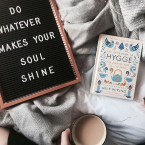 Image of a flat lay on a cosy duvet with a cup of tea, book and a candle