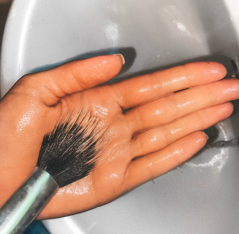 Image: Make-up brush being washed with cleanser in the palm of persons hand