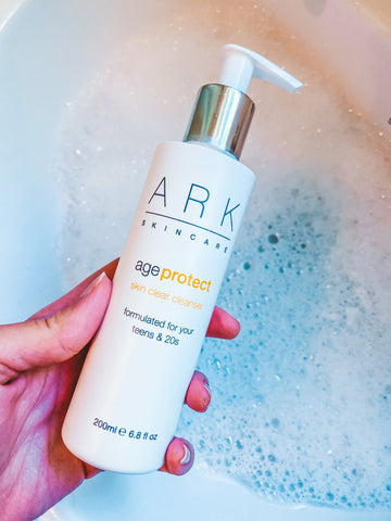 Product Image: ARK Skincare's Age Protect Vitality Cleanser held over a bubble bath