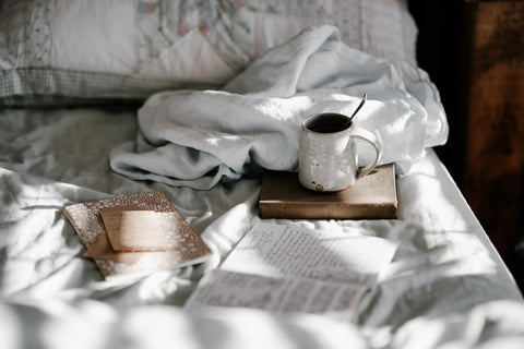 A cosy set up in a bed with a mug of coffee, a book and white cotton bed sheets