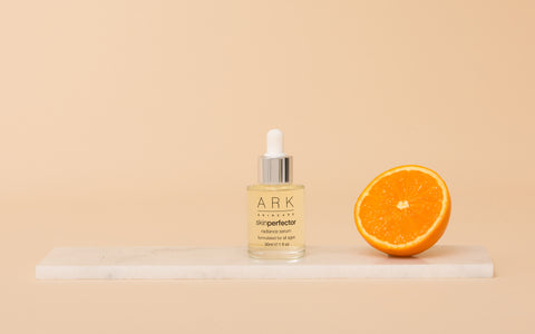Image: ARK Skincare's skin perfecting Radiance Serum on a marble slate next to an orange - one of the product ingredients.