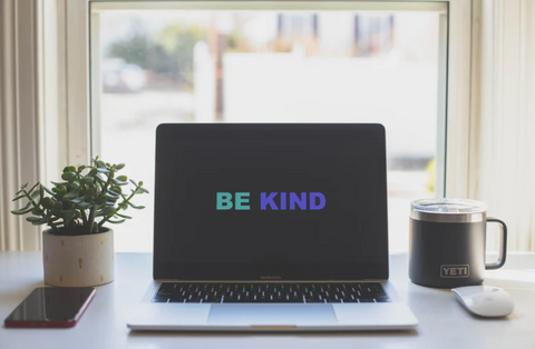 Image of a laptop screen with a 'be kind' screen saver, on a desk with coffee and a plant