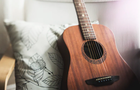 Image of a brown acoustic guitar leaning on a while pillow on a desk chair