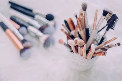 Image of freshly washed make-up brushes in a pretty white pencil pot