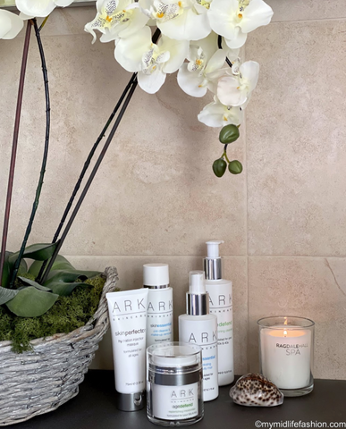Product Image of a range of ARK Skincare products on a bathroom counter next to an Orchid.