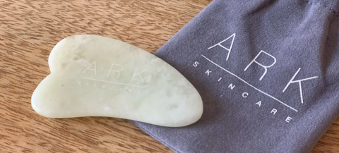 Product Image of ARK Skincare's Gua Sha Jade Tool laid on a wooden table with it's grey velvet drawstring bag