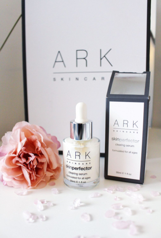 Product image of ARK Skincare's Clearing serum next to it's product box and a pretty pink rose, laid out in front of a branded ARK Skincare gift box.