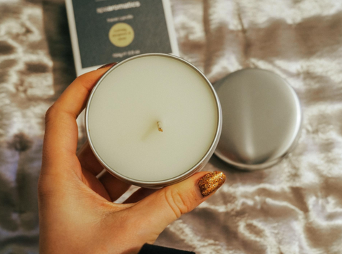 Product Image of ARK Skincare's Travel Candle being held above a cosy looking bed sheet with its branded product box.