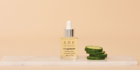 Image: ARK Skincare's Hydrating Serum in glass bottle with pipette next to slices of cucumber sitting on a marble slate.